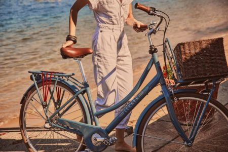 Woman wearing white jumpsuit with bicycle with basket at the beach
