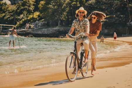Young woman and young man wearing sunglasses riding one bicycle at the beach while smiling