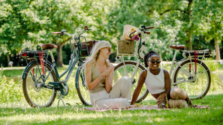 women in the park with LEKKER Jordaan+ blue and cream eBikes