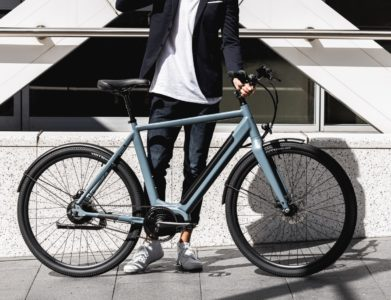 Man wearing casual clothing standing next to blue bicycle