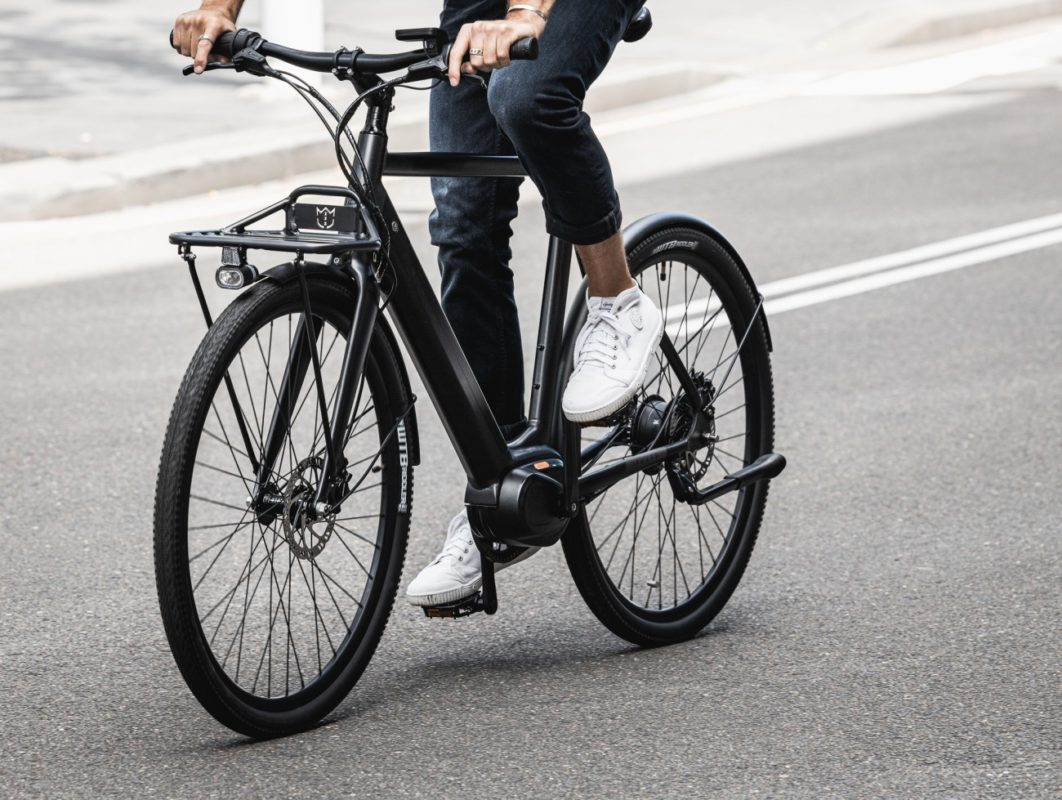 Man wearing jeans and white sneakers riding black bicycle on the street