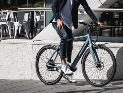 Man wearing casual clothing and white sneakers riding blue bicycle