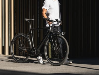 Man wearing casual clothing and white sneakers walking with black bicycle
