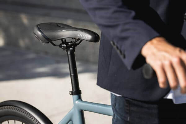 Close up of black bicycle seat of blue bicycle with man in front